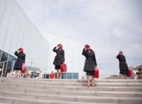 Photo of four women in red & black posing on steps
