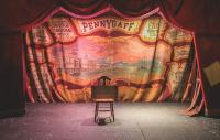 Empty stage with a period backdrop with the word 'Pennygaff' in the background and a chair in the foreground with a 'closed' sign on top