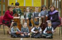 Photo of children with instruments, with Nicola Sturgeon & Fiona Hyslop