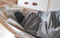 A photo of a man sleeping in a hammock