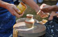 Two people creating a pot on a potter's wheel