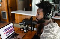 Man with headphones and microphone recording on a laptop