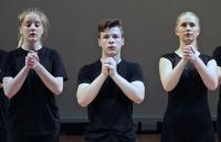 Photograph of dancers with pleading hands