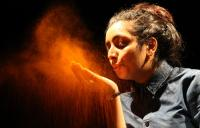 Photo of girl blowing orange powder off hand