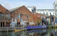 Photo of a canal boat by a warehouse