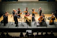 Ensemble of players on stage watched by audience