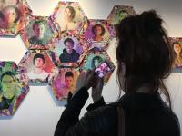 Image of woman taking a picture of collage of headshots