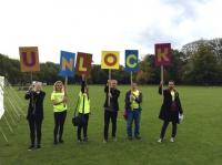Photo of people holding up letters spelling 'Unlock'