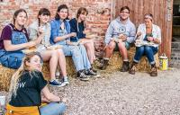 Photo of volunteers sat on haybales