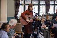 Photo of female guitarist performing in room of older people
