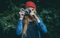 A young woman in a red hat taking a photograph