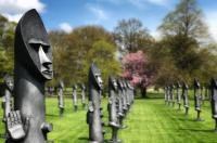 A row of black sculptures on a grass lawn