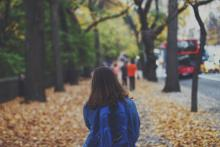 A child with a backpack walking along the road
