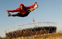 Photo of a dancer jumping in front of the Olympic stadium