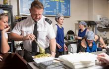 A photo of a member of Merseyside Police force working in a local chip shop