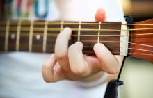A close up of a person's hand playing the guitar