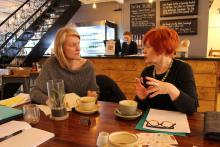 Photo of two women in conversation in a cafe