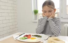Photo of a girl sitting in front of a plate of food