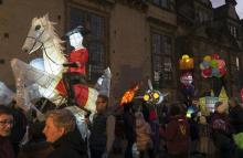 A crowd of people on a street holding illuminated paper sculptures