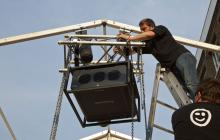 a man installing audio visual equipment high up on an outdoor stage