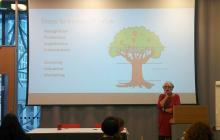 Photo of Ruth Soetendorp presenting in front of an image of a tree