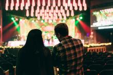 Silhouette of two people watching a live performance