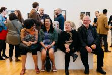 People sitting on a bench in the middle of an art gallery