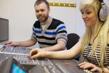 Man teaching woman on audio mixer