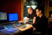 Two people working on a soundsboard