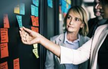 A photo of two women looking at sticky notes on a wall