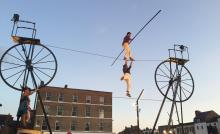 Photo of tightrope walkers in city street
