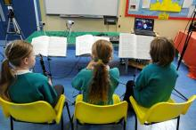 Photo of children having music lesson via internet