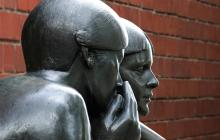 A photo of a statue of a person whispering into someone's ear