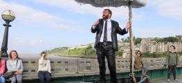 Performance shot: man in boat under a raining umbrella