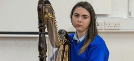 You girl in school uniform playing harp