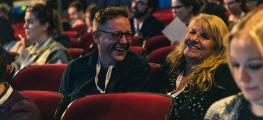 A photo of a man and a woman laughing in an auditorium