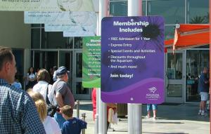 People queuing for an aquarium amongst membership signs
