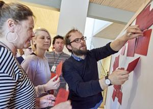 Photo of people sticking notes to whiteboard