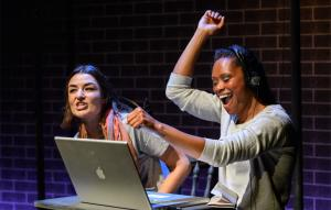 Photo of two women, one is celebrating with here hand in the air in front of a macbook