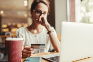 Woman debating online purchase with credit card