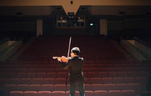 Performer playing violin to an empty theatre