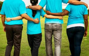 People from different ethnicities and genders linked arm in arm, photographed from behind