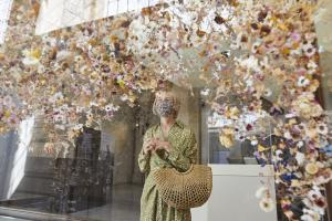 A woman in a floral dress and face mask looking an art installing of floating flowers