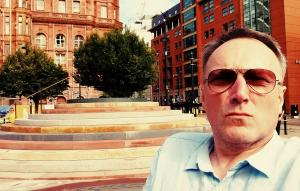photo of Andrew Miller beside Jeremy Miller's Peterloo Memorial in Manchester