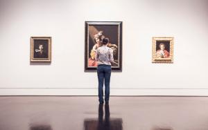 a women looks at paintings in galleries