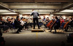 an orchestra performing in a multi-storey car park