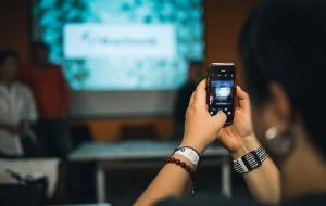 A person taking a photo of a presentation with their smartphone