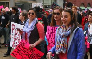 A photo of a protest march with women holding signs
