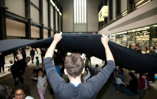 Photo of people holding a large black square of fabric in the Turbine Hall