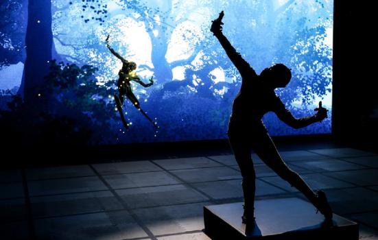Silhouette of someone in a motion capture suit and their digital projection in a forest, in the background.